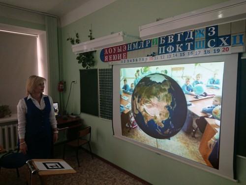 Учитель показывает объект Земля технологии дополненной реальности
